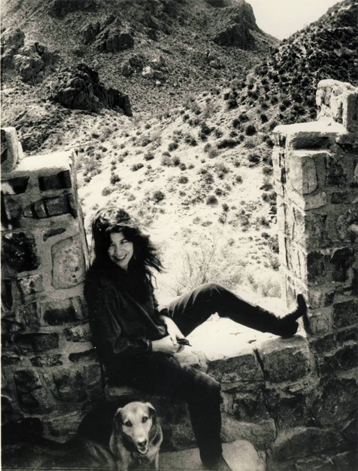 Poet Joy Harjo sits in the square frame of a brick wall in the desert, one leg on the sil. There is a dog sitting on the ground in front of her