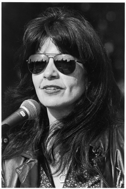 Poet Joy Harjo in front of a mic on stage wearing sunglasses with a city skyline reflected in them