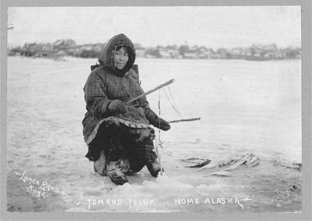 Black and white photograph of an Eskimo woman holding two rods for ice fishing and smiling slightly at the camera. She has caught a fish.